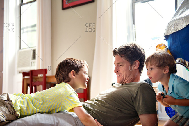 Father and sons playing in kid's room.
