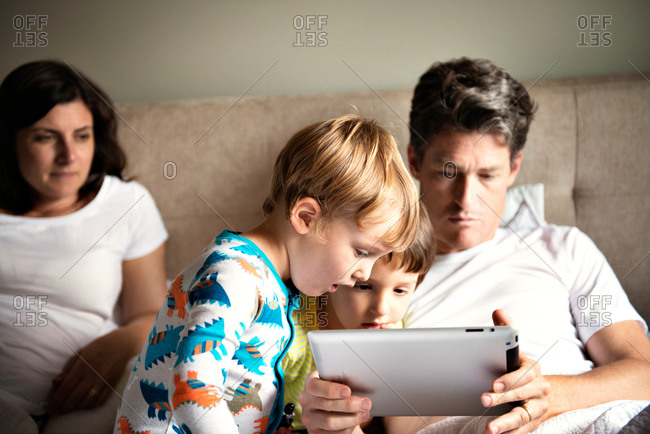 Family resting in bed while watching tablet computer.