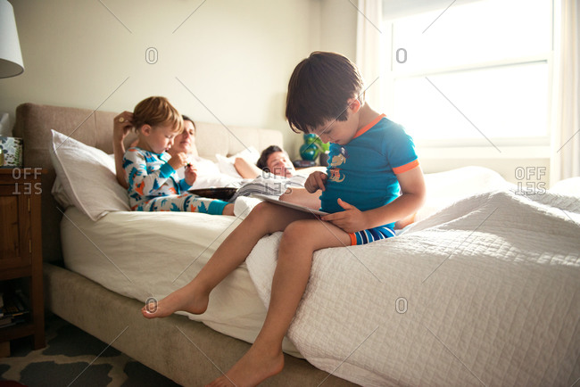 Boy playing on tablet computer while mother, father and younger brother resting in  bed.