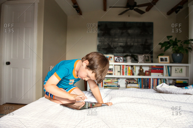 Boy playing on tablet in bedroom