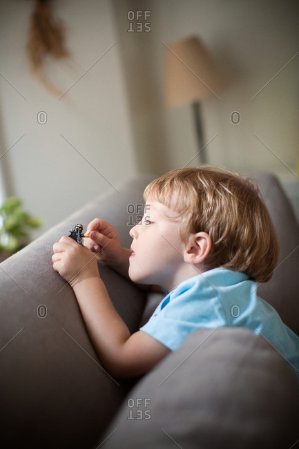Little boy playing with little toy on gray couch