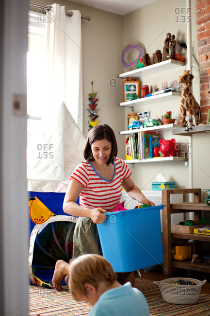 Mother holding blue plastic storage box in kid's room.