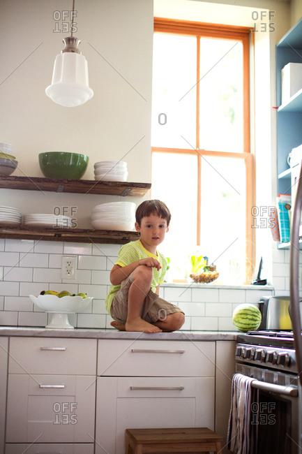 Little boy kneeling on counter in kitchen.