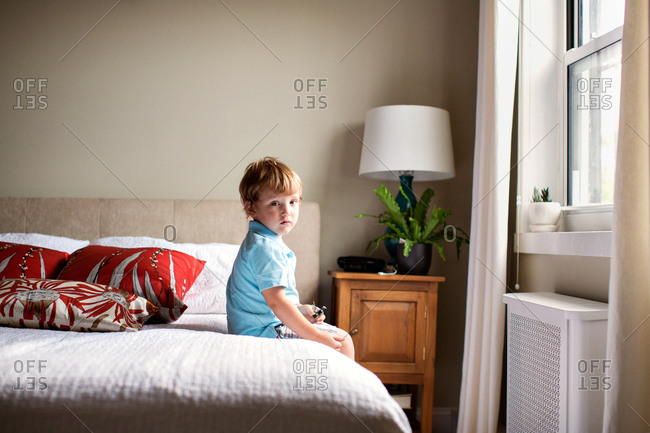 Little boy sitting on his parents bed in bedroom