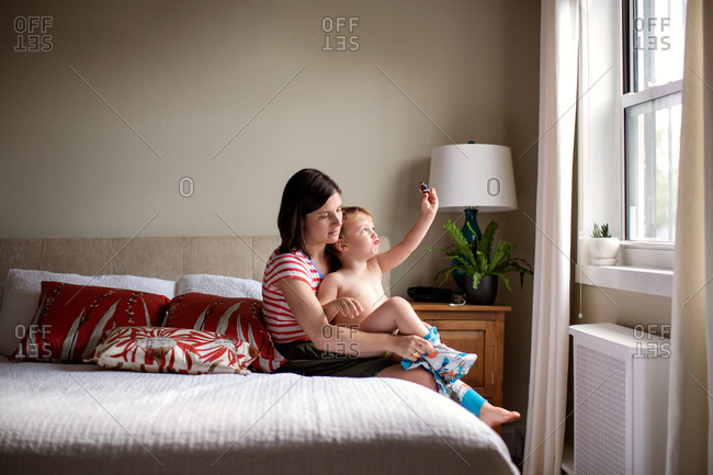 Mother dressing her son in bedroom.