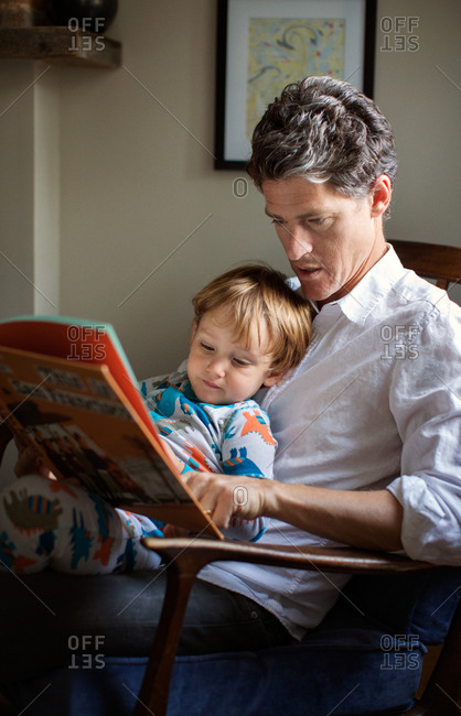 Father sits in armchair holds his boy in lap reads book