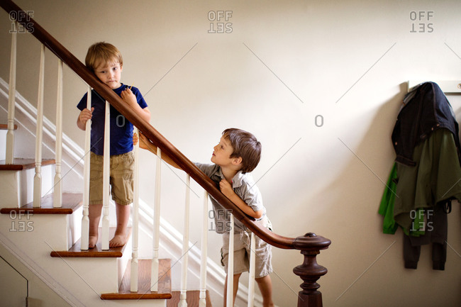 Siblings standing on stairs, leaning on handrail