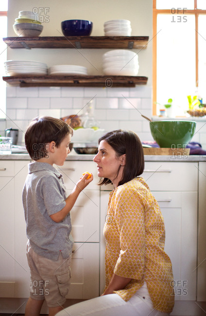 Mother and her son having serious conversation in kitchen.