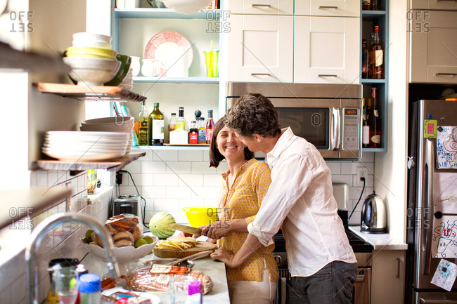 Happy couple standing in kitchen