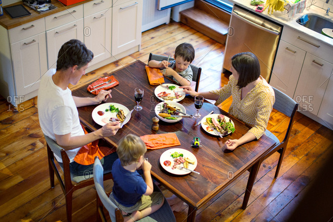 Overhead view of family eating dinner in kitchen