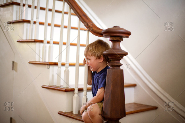 Little boy sitting on step next to banister and crying.