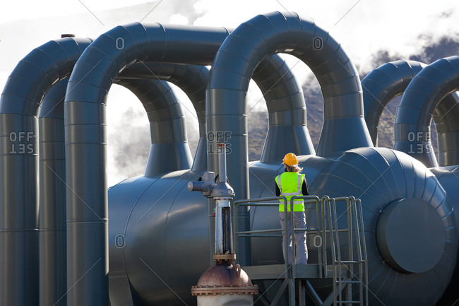 Woman engineer standing at geothermal plant, Iceland