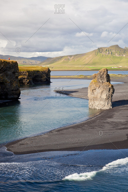 Woman standing on cliff at Reynisdrangar cliffs, Dyrholaey, Iceland