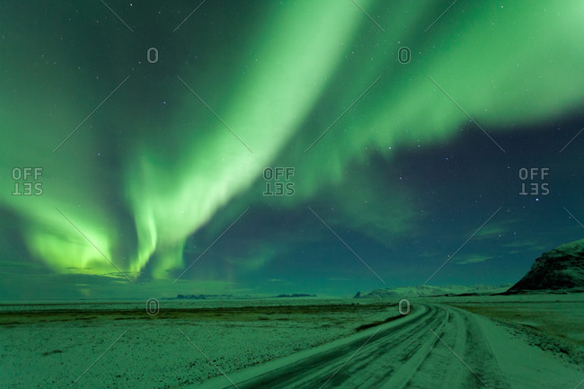 Northern Lights above winter road in Iceland