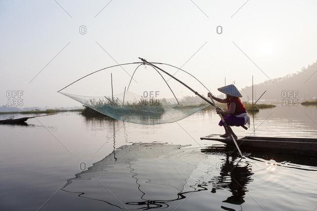 Fisherman paddling boat on Loktak Lake in Imphal, Manipur, India