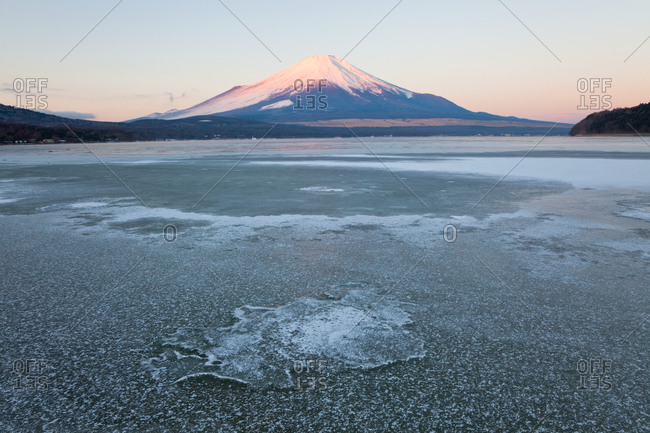 Ice on Lake Yamanaka with snow covered Mount Fuji in background, Japan