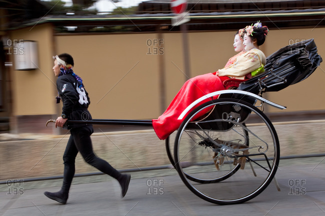 Geishas traveling in a rickshaw on the street of Kyoto, Japan