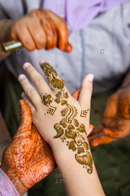 Henna tattoos being put on hands in Essaouira, Morocco
