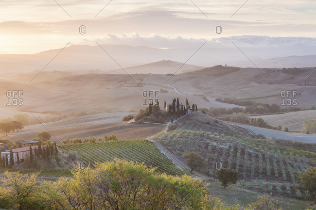 Val d'Orcia, Italy - September 26, 2012: Sunset over green fields