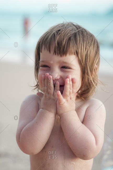 A little girl at the beach, laughing and putting her hands to her face