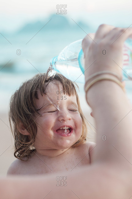 A little girl at the beach, laughing with closed eyes as water is being poured over her face from a bottle