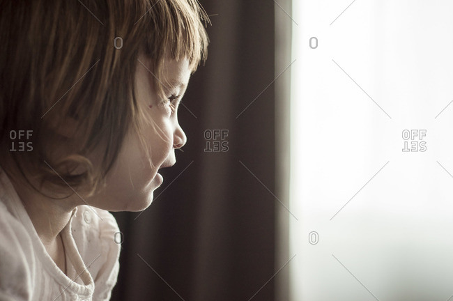 A little girl looking out a window and smiling