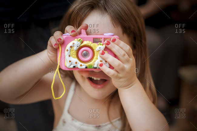 A little girl holds a toy camera to her face