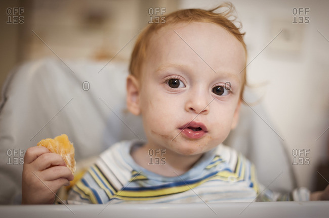 A red headed little boy is holding a half-eaten orange in one hand,  his face dirty with food