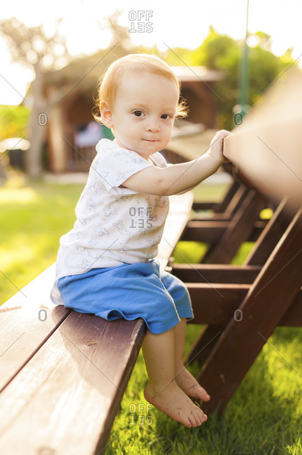 A little boy is sitting at a long wooden table outdoors