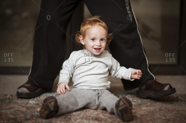 A red headed little boy is sitting on a carpet, facing the camera and smiling
