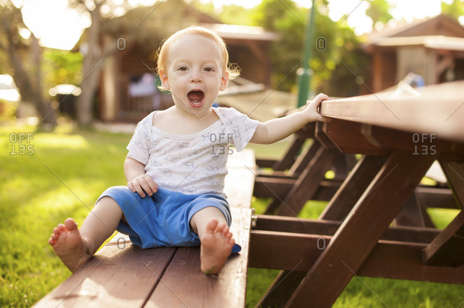 A little boy is sitting on a bench next to a long wooden table