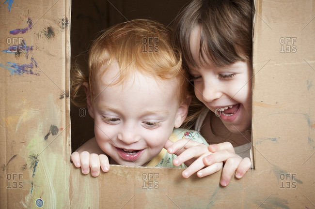 A little red headed boy and a little brunette girl are peeking from a hole cut-out from a large cardboard box