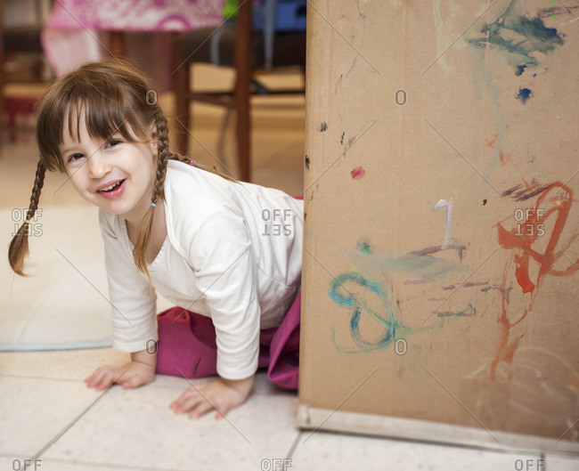 A little brunette girl with pigtails is on her knees, smiling, and peeking from behind a large cardboard box