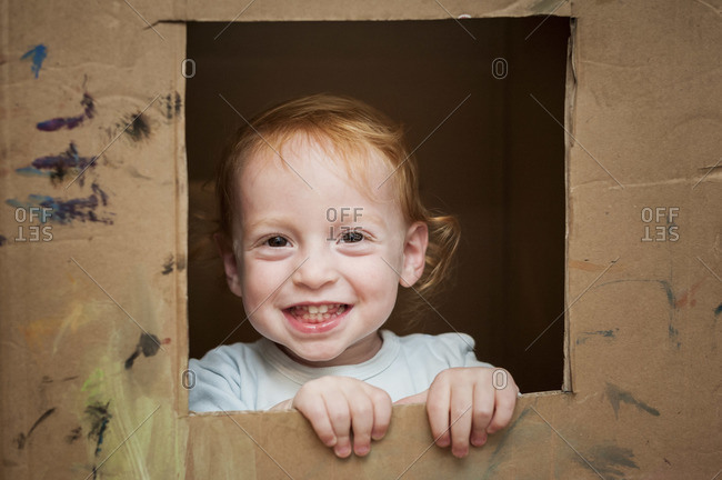 A little red headed boy is peeking from a hole cut-out from a large cardboard box