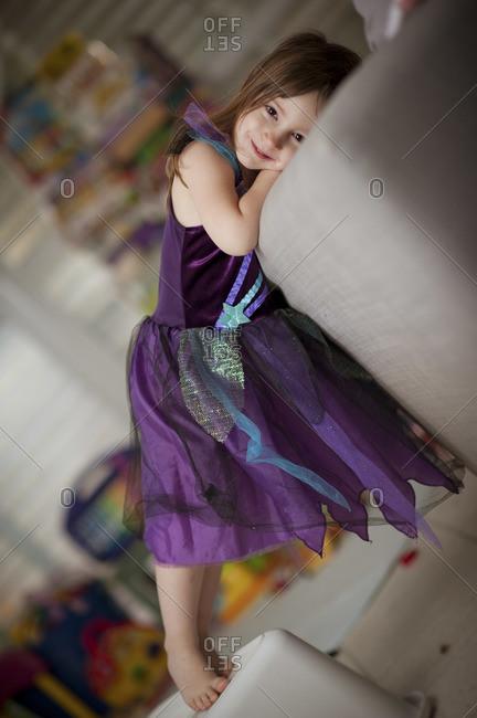 A little brunette girl leaning against a sofa, wearing a purple dress