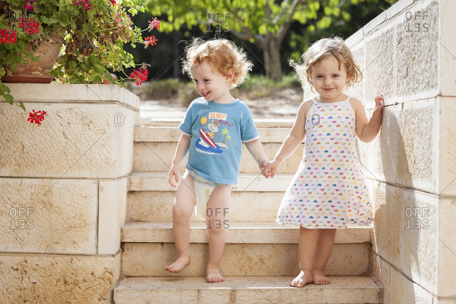 A little boy and girl are walking down stone stairs, holding hands