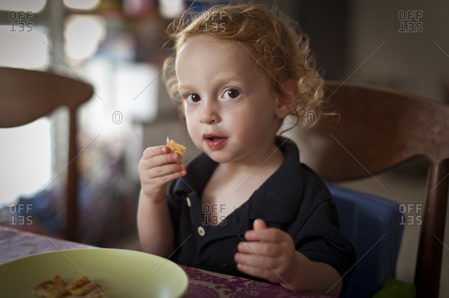A little red headed boy is sitting at a table and eating, while looking at the camera