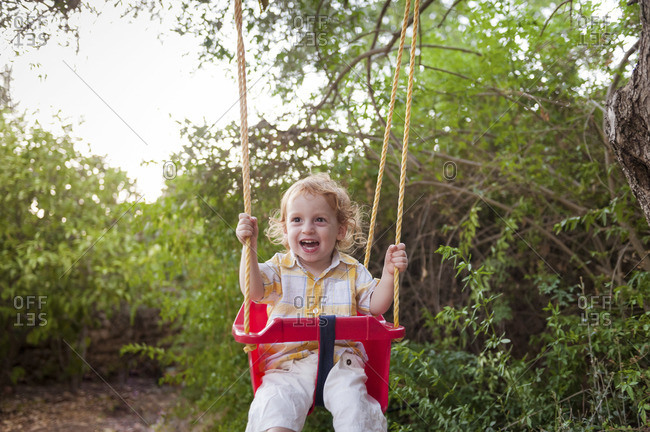 A red headed toddler boy is sitting on a red plastic swing