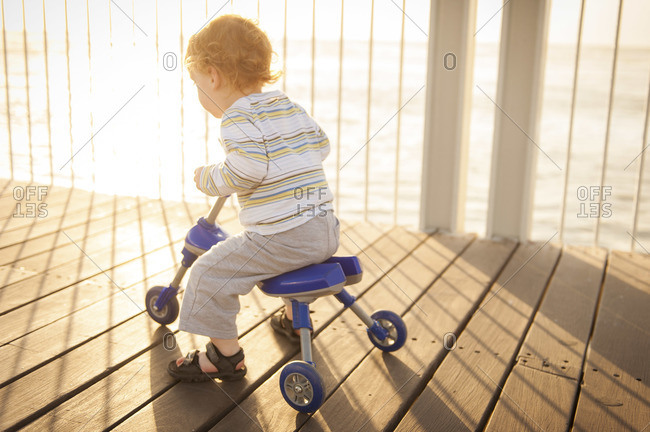 A little red-headed boy riding a small tricycle on a wooden bridge, with the sun shining behind him