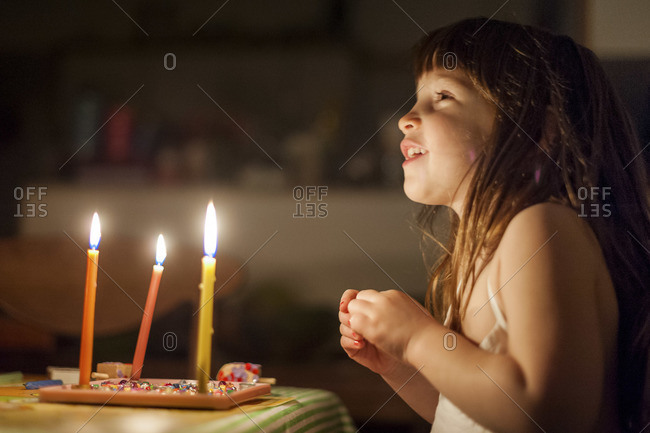A little girl is sitting in a dark room in front of 3 burning candles, smiling and holding her hands