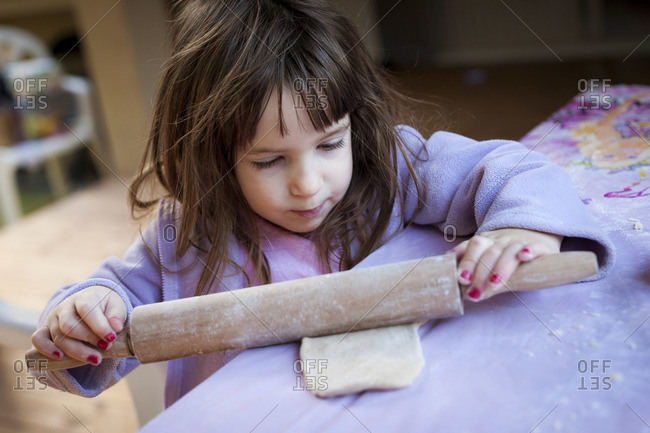 A little girl using a rolling pin to work the dough