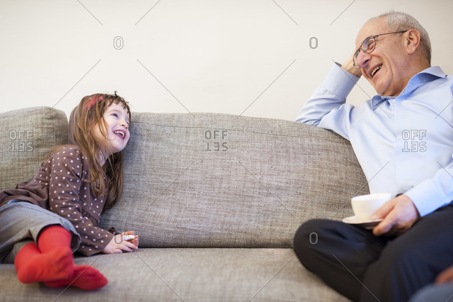 A grandfather and his granddaughter are sitting opposite each other on a long couch