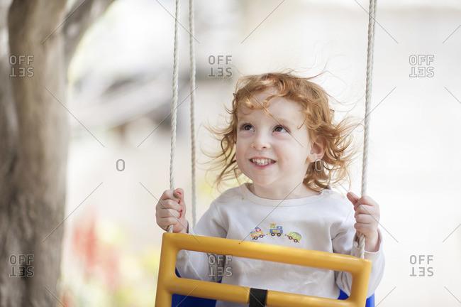 A red headed little boy sitting on a swing
