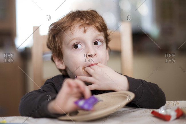 A little red headed boy is eating a candy