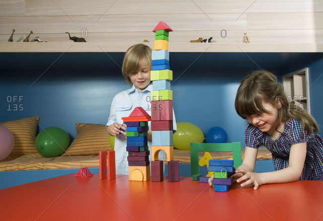 Boy (8-9) and girl (6-7) playing building bricks, portrait