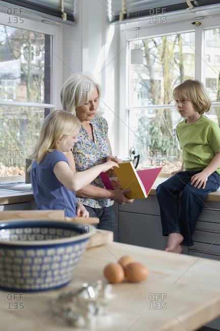 Grandmother and grandchildren (8-9) in the kitchen
