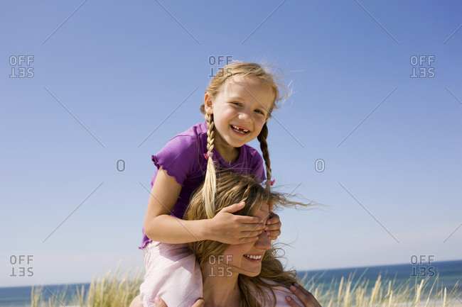 Germany, Baltic sea, Mother carrying daughter (6-7) on shoulders, portrait