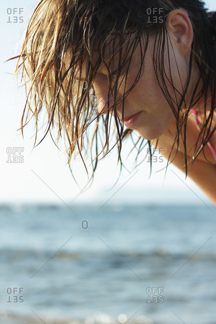 Italy, Sardinia, Woman on beach looking down, side view, portrait