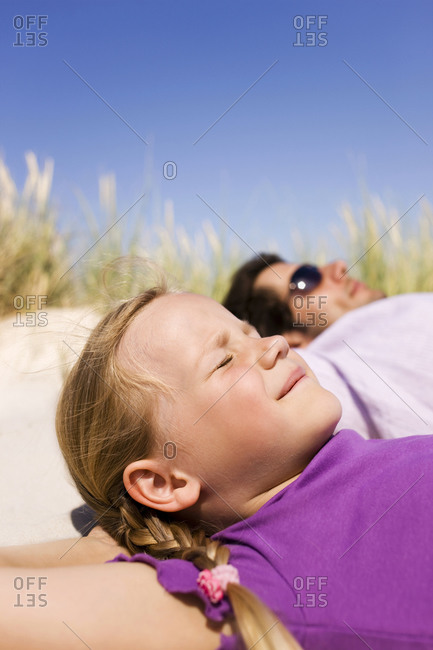 Germany, Baltic sea, Father and daughter (6-7) lying in beach dunes, portrait
