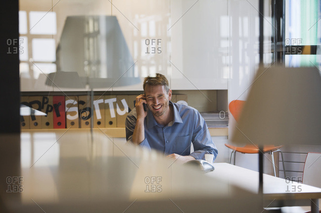 Young man in office using telephone